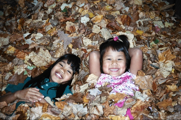 Playing in the leaves with older sister, Melanie (right), age 7